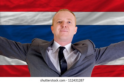 joyful investor spreading arms after good business investment in thailand, in front of flag