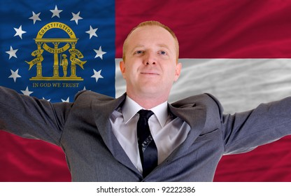 joyful investor spreading arms after good business investment in georgia, in front of flag