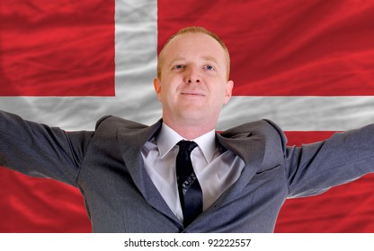 joyful investor spreading arms after good business investment in denmark, in front of flag