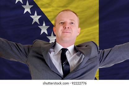 joyful investor spreading arms after good business investment in bosnia herzegovina, in front of flag