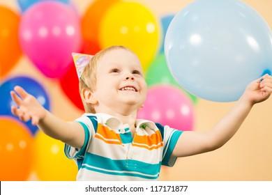 joyful kid boy with balloons on birthday party