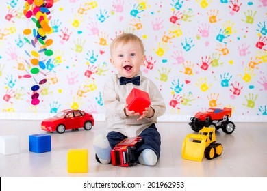 joyful kid boy on birthday party with toy cars and blocks in the bright room have a fun game