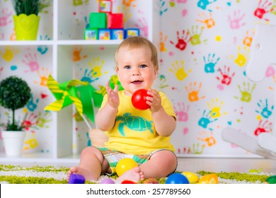 joyful kid boy on birthday party with toy balls and blocks in the bright room have a fun game