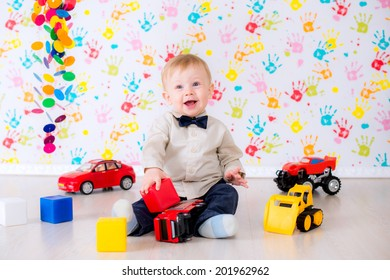 joyful kid boy y with toy cars and blocks in the bright room have a fun game