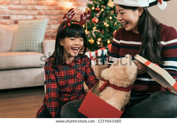 joyful kid laughing received teddy bear as christmas gift. family celebrate xmas eve lifestyle concept. happy parent and child staying sitting on the wooden floor.