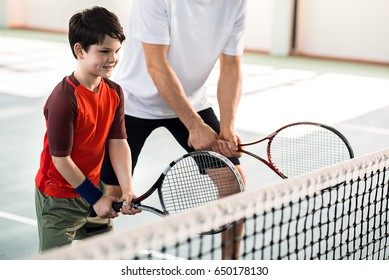 Joyful kid playing tennis with father