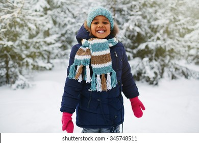 Joyful kid in winterwear looking at camera in natural environment in winter