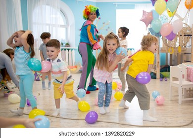 joyful kids and clown playing with color balloon on birthday party