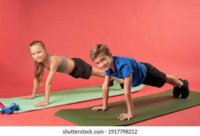 Joyful kids doing plank exercise against red background
