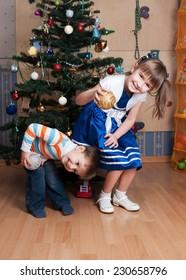 Joyful kids playing in a Christmas tree (3 years and 6 years)