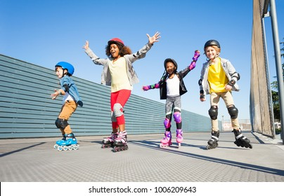 Joyful kids rollerblading outdoors at sunny day