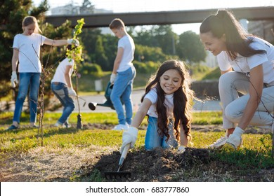 Joyful kids watering new tree