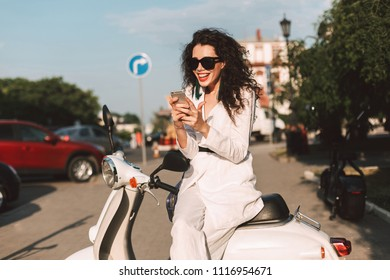 Joyful lady with dark curly hair in white costume and sunglasses sitting on white moped and happily using her cellphone on street with city view on background