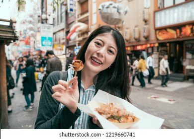 joyful lady traveler showing takoyaki to the camera. young girl cheerful trying japanese street food. travel in dotonbori in osaka japan.