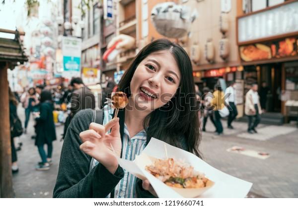 joyful lady traveler showing takoyaki to the camera. young girl cheerful trying japanese street food. travel in dotonbori in osaka japan.