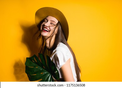 joyful laughing girl in a fashionable hat holds a green plant in hands posing on a yellow background
