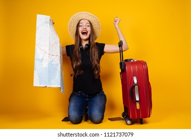 joyful laughing girl in a hat travels to different countries, holds a card, next to a large suitcase