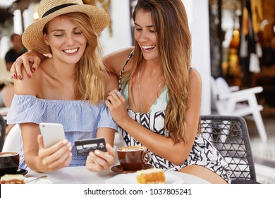 Joyful lesbian couple sit against cafe interior and drink aroma hot beverage, embrace each other, happy to recieve salary, make shopping online via modern mobile application, use free internet