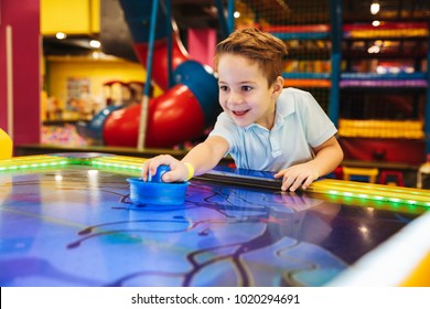 Joyful little boy playing air hockey at Arcade centre