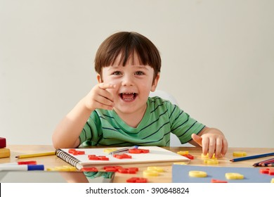 Joyful little boy sitting at desk and looking at camera