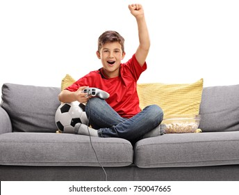 Joyful little boy sitting on a sofa and playing a soccer video game isolated on white background