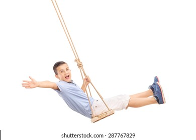 Joyful little boy swinging on a swing and gesturing happiness isolated on white background