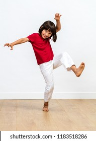 joyful little child playing monster or tiger with kid's tai chi or kung fu sporty gestures, showing kid's fighting body language over wooden floor, white background