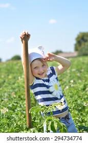 Joyful little girl with cute face working in potato field.