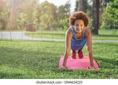 Joyful little girl doing plank on yoga mat in park