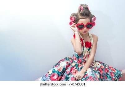 Joyful little girl with hair curlers and red sunglasses. Kid's fashion