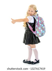Joyful little girl showing thumbs up on white background. The concept of school and education, children's emotions. Isolated.