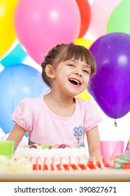 Joyful little kid girl at birthday party