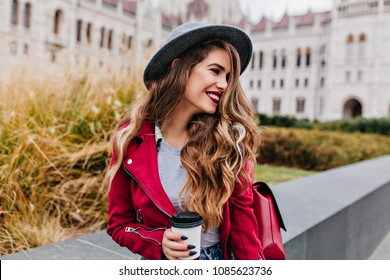 Joyful long-haired woman with trendy black manicure looking away while waiting someone near old building. Photo of pretty caucasian female model in hat drinking coffee outdoor.