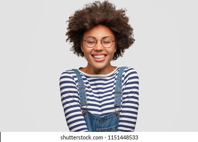 Joyful lovely dark skinned female with pleased expression, has broad smile, closes eyes in happiness, wears fashionable overalls, expresses positive emotions, isolated over white background.
