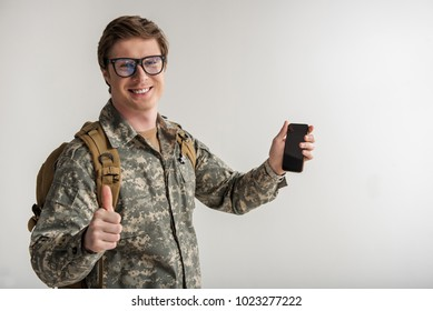 Joyful male cadet looking at camera and holding mobile phone. He is smiling and showing that everything is fine. Isolated on background