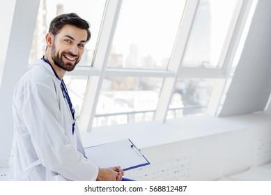 Joyful male general practitioner relaxing near window