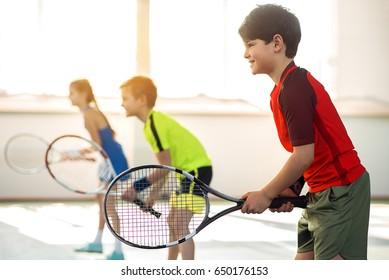 Joyful male kid playing tennis with friends