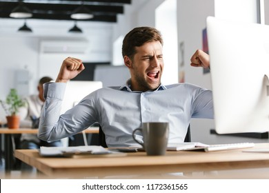 Joyful male manager rejoices and using computer while sitting by the table in office