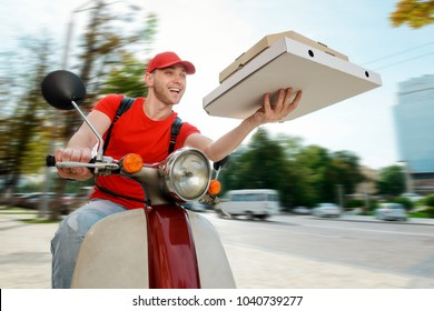 Joyful man is delivering pizza. Deliveryman uses a company motorbike to reach a customer. Order fast food online.