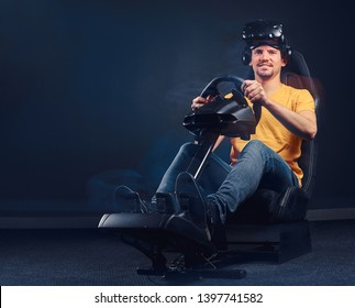 Joyful man dressed in yellow shirt and jeans in VR headset sitting on a car racing simulator, looking at camera.