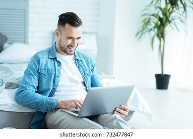 Joyful man grinning broadly while using laptop