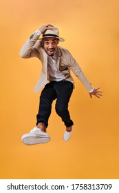 Joyful man in hat is jumping on orange background. Snapshot of guy in black pants, jacket and whie tee dancing and smiling on isolated