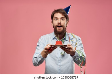 joyful man in a holiday hat holding a cake on a pink background, birthday
