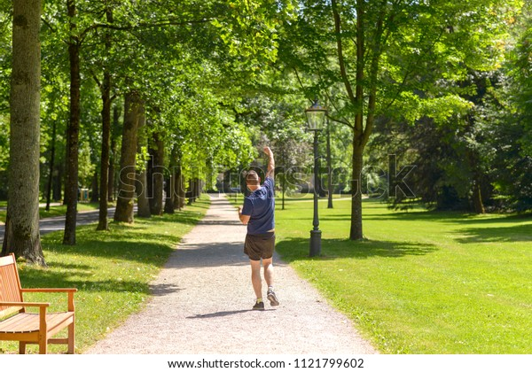 Joyful man jogging in a wooded green spring park running away from the camera punching the air with his fist as he enjoys his daily workout