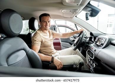 Joyful man locating in modern automobile
