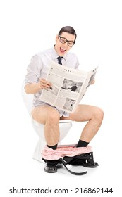 Joyful man reading the news seated on a toilet isolated on white background