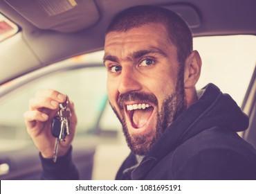Joyful man shows the keys to his new car