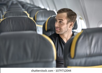Joyful man sits in the airplane next to the window on the background of the empty seats. He wears a black T-shirt and looks to the side with a smile. Closeup. Horizontal.