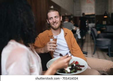 Joyful man sitting in restaurant and talking with girl. Smiling boy sitting at cafe with glass of water in hand. Young man with blond hair and beard talking with friend in restaurant