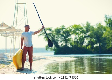 Joyful man stands on the beach with a SUP board is delighted with the sunny morning and enjoying life. Stand up paddle boarding - awesome active outdoor recreation.